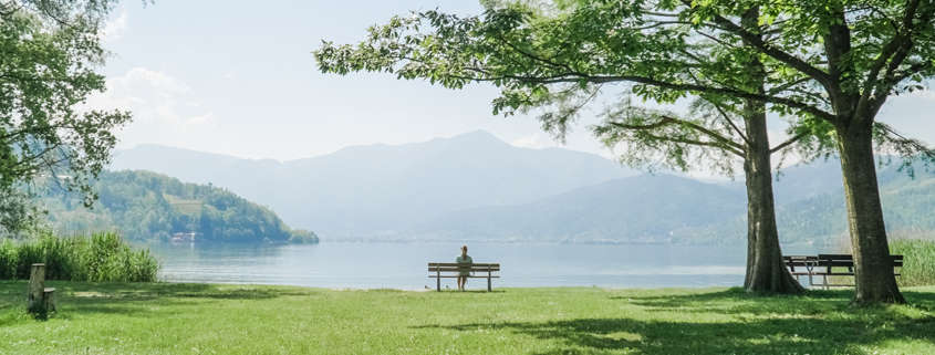 A person sits on a bench in an empty field, looking over the mountains