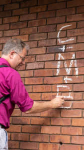 "Bishop Steven writes ""C+M+B"" on a brick wall in chalk"